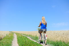 Backview of beautiful young woman cycling in sunny Royalty Free Stock Image