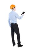 Backview of business man in construction helmet stands and enjoy Stock Photos