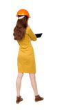 Backview of business woman in construction helmet stands and enj Royalty Free Stock Photos