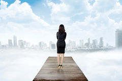 Backview of business woman looking the city from wooden pier Stock Photos
