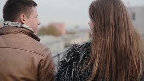 Backview of a dark-haired couple, having a walk on a roof, kissing, talking. Harmony in relationship. Happy relationship. Backview of a dark-haired loving stock footage