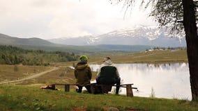 Backview de dois indivíduos adultos, sitts no banco e do gasto pelo olhar tempo ao redor na beleza do lago da montanha video estoque