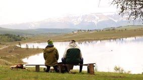Backview de dos individuos adultos, sitts en el banco y del gasto por mirada tiempo alrededor en la belleza del lago de la montañ almacen de video