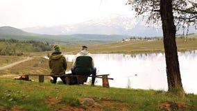 Backview de dos individuos adultos, sitts en el banco y del gasto por mirada tiempo alrededor en la belleza del lago de la montañ almacen de metraje de vídeo
