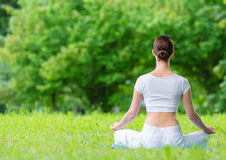 Backview de femme dans faire des gestes de zen de position de lotus image libre de droits
