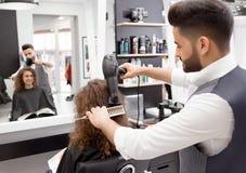 Backview de hairstyler faisant des hairdress pour le client féminin bouclé de sourire photos libres de droits