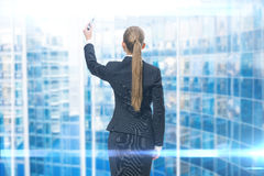 Backview de l'écriture de femme d'affaires sur l'écran bleu Photos stock