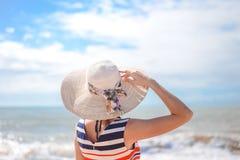 Backview de la señora elegante en el sombrero de paja que se coloca encendido imagen de archivo