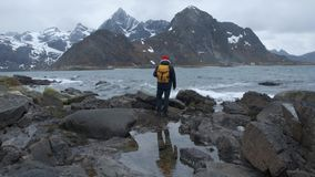 Backview de um indivíduo só ir e para olhar ao redor nas imagens da beleza da área de mar selvagem Tempo ventoso frio filme