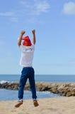 Backview del niño pequeño alegre en el salto del sombrero de Papá Noel Fotografía de archivo
