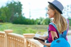 Backview dello studente grazioso che si siede con un libro vicino al fiume Fotografie Stock Libere da Diritti