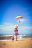 Backview der Frau Regenschirm mit Baby halten Stockfotos