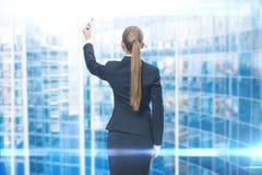 Backview des Geschäftsfrauschreibens auf blauem Schirm stockfotos