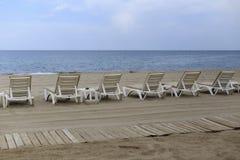 Backview des lits pliants blancs à la plage sablonneuse Image stock