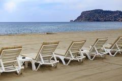 Backview des lits pliants blancs à la plage sablonneuse Images stock