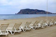 Backview des lits pliants blancs à la plage sablonneuse Photos stock