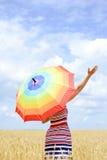 Backview des Mädchens mit dem Regenschirm, der in Goldenem steht Stockfoto