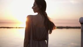Backview eines langhaarigen hübschen Mädchens, das im Kleid steht auf einem Pier während des schönen Sonnenuntergangs oder des So stock video