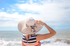 Backview of elegant lady in straw hat standing on Stock Image