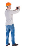 Backview of an engineer in construction helmet stands and enjoys Royalty Free Stock Photography