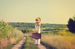 Backview of exciting young woman with suitcase Stock Images