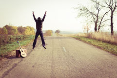 Backview of guitar player in hat jumping on Stock Images