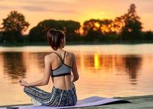 Backview jogging девушки около озера на заходе солнца Стоковые Изображения