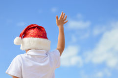 Backview of kid in red Santa hat with raised hand Stock Photo