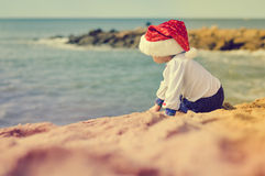 Backview of little kid in Santa hat on sunny Royalty Free Stock Image