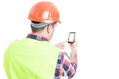 Backview of male engineer holding mobile phone Stock Photography