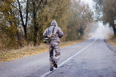 Backview of man in camouflage running on autumn Stock Images