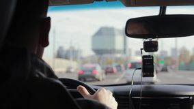 Backview of a man driving a car in a city. Blurred sights. Big interesting building in the distance. Traveling by car. Traveling by car. Backview of a man stock video