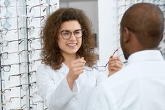 Backview of man trying on eyeglasses in optical shop. stock photo
