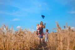 Backview of mother and two kids in summer wheat Stock Images