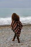 Backview stående av den lyckliga brunettkvinnan på stranden som bär p Fotografering för Bildbyråer