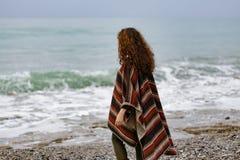 Backview stående av den lyckliga brunettkvinnan på stranden som bär p royaltyfri bild