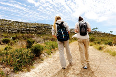 Backview of two young women hiking in nature. Two girls walking outdoors and having fun exploring the wilderness royalty free stock image