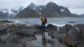 Backview van één eenzame kerel door te gaan en kijkt rond op de schoonheidsbeelden van wild zeegebied Koud winderig weer stock footage