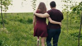Backview van een houdend van paar die in een tuin lopen Koesterend minnaars geniet aard van Langzame mo, steadicam schot stock footage
