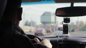 Backview van een mens die een auto in een stad drijven Vage gezichten Het grote interesseren inbouwend de afstand Het reizen door stock video