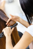 Backview van herenkapper die haarstijl voor vrouw doen stock foto's