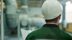 Backview van ingenieur in bouwvakker die in fabriek lopen en op klembord neerschrijven stock footage