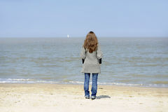 Backview of young woman on the beach Stock Photo