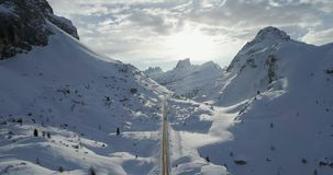 Backward aerial along road in snowy valley at Valparola pass.Sunny sunset or sunrise, cloudy sky,backlit sun.Winter stock footage