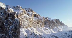 Backward aerial along snowy alpine steep rocky cliff valley.Sunny day,clear sky.Winter Dolomites Italian Alps mountains stock video