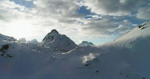 Backward aerial from snowy mounts at Valparola pass.Sunny sunset or sunrise, cloudy sky with backlit sun.Winter stock footage
