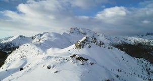 Backward aerial from snowy mounts at Valparola pass.Sunny sunset or sunrise, cloudy sky.Winter Dolomites Italian Alps stock video footage