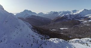 Backward aerial to snowy alpine valley with woods forest at Valparola pass.Sunny sunset or sunrise,clear sky.Winter stock video footage
