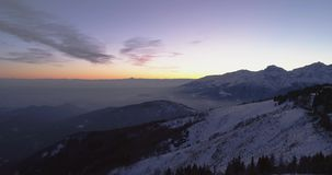 Backward aerial top view over winter snowy mountain with car travelling on road.Blue hour dusk or dawn twilight Alps. Mountains street path snow establisher.4k stock footage
