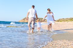 Backward Happy family of three - mother, father and daughter holding hands and having fun walking on the beach. Family vacation, t. Ravel concept. Bright Royalty Free Stock Photo